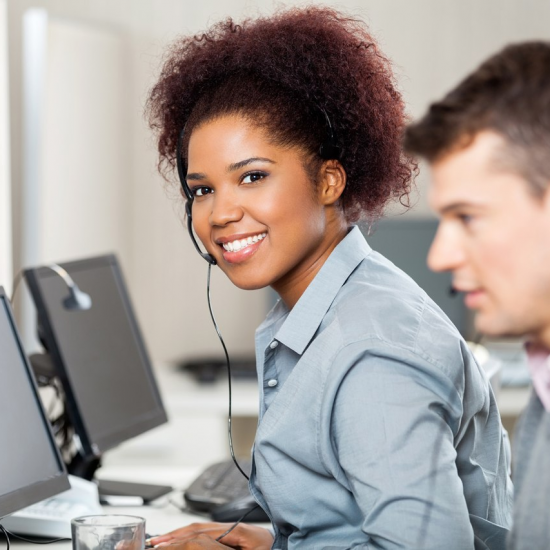 Woman and man at computers with headsets on